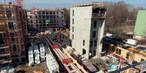 Blick auf eine beengte Großbaustelle, auf der fünf Gebäude parallel entstehen